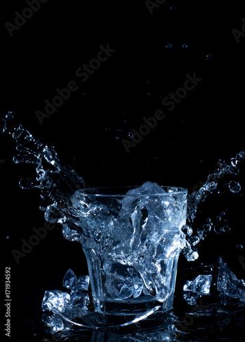 kostka-lodu-spadajaca-do-wody-na-ciemnym-tle
