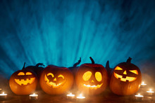 Halloween Pumpkins In A Row With Candles Over Blue Light Rays And Smoke At Background With Copy Space For Text Above, Front View