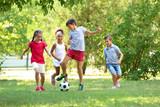 Fototapeta Kuchnia - Cute children playing football in park