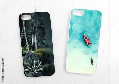 Two black and white phone cases on white wood with landscapes, topview