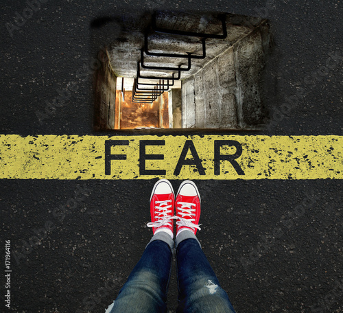 Photo Girl standing in front of the FEAR sign and a well that scares