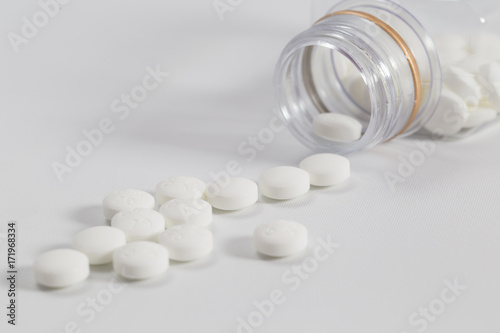 White Pills Pouring Out Of The Medicine Bottle On A White