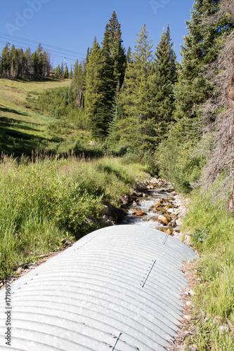 Valokuva  Stream through a metal corrugated culvert in Colorado