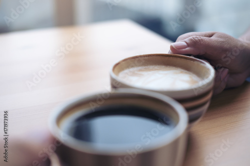 Fotografie, Obraz  Close up image of two people clink coffee cups on wooden table in cafe