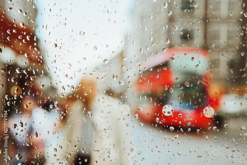 Photo  Raindrop on glass and red London bus lights background.