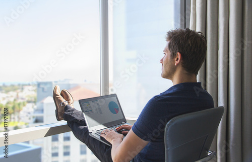 Young businessman in casual attire working on laptop at home office Canvas Print