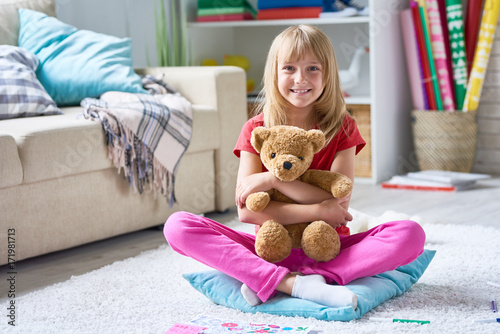 Full length portrait of pretty little girl looking at camera with toothy smile while sitting in lotus position on carpet and hugging plush teddy bear, interior of cozy living room on background