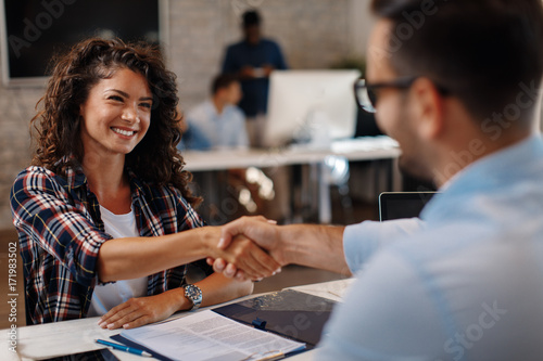 Fotografia  Young woman signing contracts and handshake with a manager