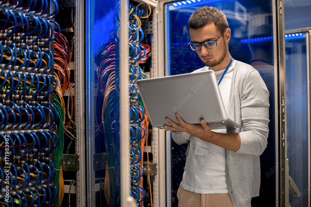 Fototapeta Portrait of modern young man holding laptop standing in server room working with supercomputer in blue light