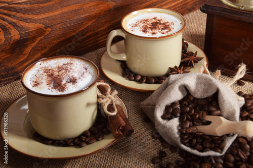 Foto op Plexiglas Chocolade coffee with milk and chocolate foam in brown ceramic cups with vanilla and coffee grains