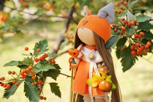 Handmade Doll Girl In Orange Dress Holding Fox, Mushrooms And Acorn In The Background Of Autumn Foliage. Autumn.