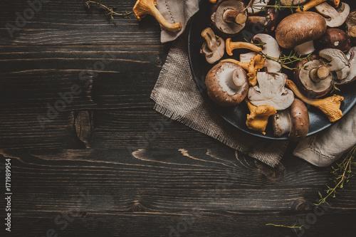 Fototapeta Fresh mixed forest mushrooms on the wooden black table obraz