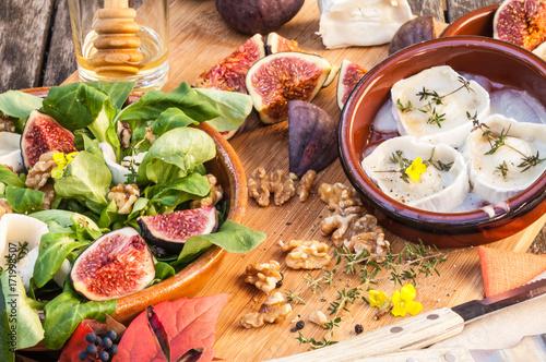Keuken foto achterwand Assortiment Angerichteter Feldsalat mit frischen Feigen, Ziegenkäse mit Honig und Walnüssen