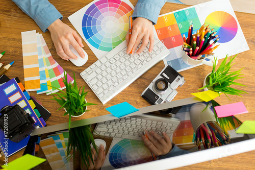 Fototapeta Young cute Graphic designer using graphics tablet to do his work at desk