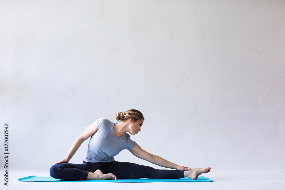 Fotografia Young beautiful woman in sportswear doing stretching while sitting on the floor on yoga mat