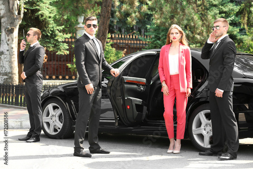 Fotomural  Famous celebrity with bodyguards near car outdoors