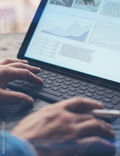 Wallpaper Mural Closeup view of male hands typing electronic tablet keyboard-dock station
