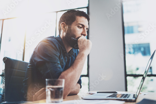 Young coworker working at sunny work place loft while sitting at the wooden table.Man analyze document on laptop display.Blurred background.Horizontal.