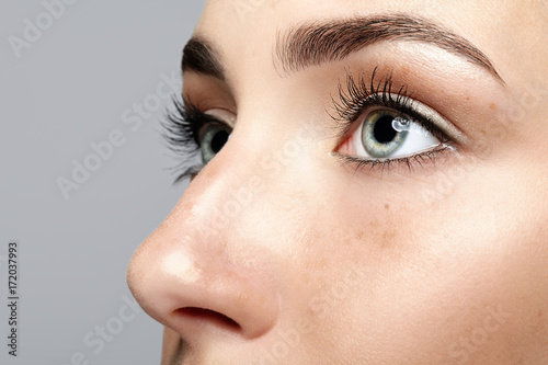 Closeup macro portrait of female face. Human woman open eyes with day beauty makeup. Girl with perfect skin and freckles