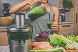 Woman juicing making green juice with juice machine in home kitchen. Healthy detox vegan diet with vegetable cold pressed extractor to extract nutrients for smoothie drink.