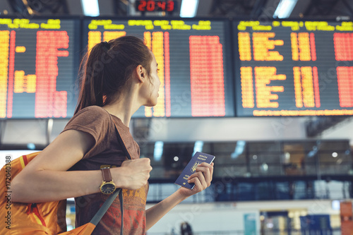 Spoed Foto op Canvas Muziekwinkel Young woman with small backpack as a hand luggage in international airport looking at the flight information board, checking her flight