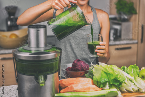 Poster Sap Woman juicing making green juice with juice machine in home kitchen. Healthy detox vegan diet with vegetable cold pressed extractor to extract nutrients for smoothie drink.