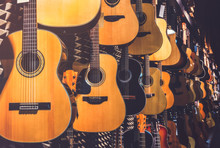 Many Classical Guitars Hanging On Wall In The Shop