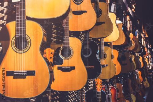 Photo Stands Music store Many Classical Guitars Hanging on Wall in the Shop