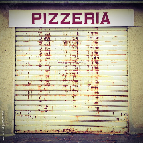 sign PIZZERIA text with closed gate