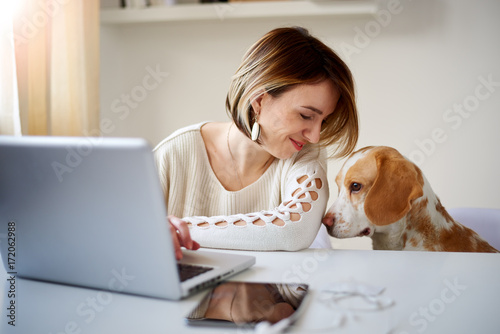 Poster  Caucasian businesswoman playing with dog in home office