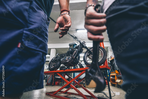 Man biker with tattoos poses with mechanic in workshop - Buy this
