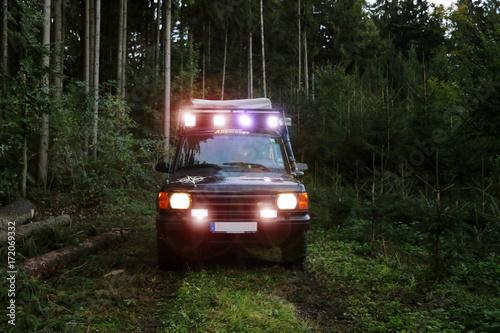 Cuadros en Lienzo Geländewagen im Wald mit LED Licht