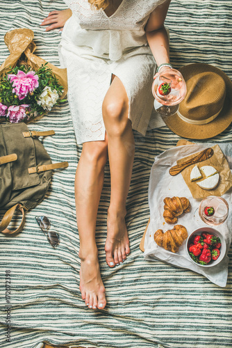 Keuken foto achterwand French style romantic picnic setting. Woman in white dress with glass of wine, fresh strawberries, croissants, brie cheese, sunglasses, peony flowers on blanket, top view. Outdoor gathering concept