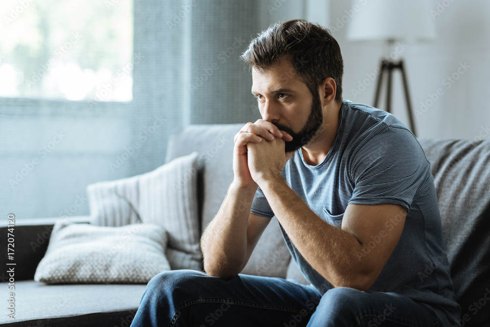 Fototapety, obrazy: Unhappy bearded man sitting on the sofa