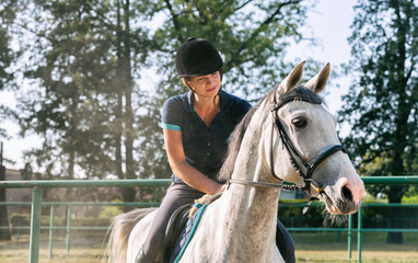 Woman riding a horse on paddock, horsewoman sport wear