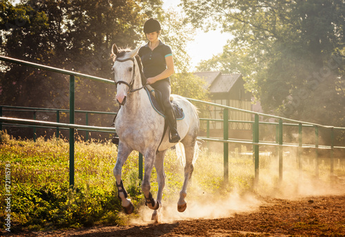 Photographie Woman riding a horse in dust on paddock