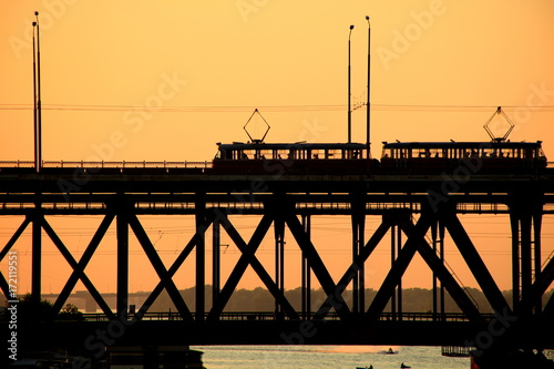 Photo  Silhouettes of a two-tiered bridge and 2 trams on a sunset ,  Dnepr city, (Dnepr