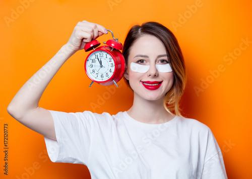 Obraz na płótnie Woman using eye patch for her eyes and holding alarm clock