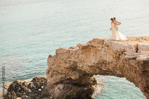 Foto op Plexiglas Cyprus beautiful gorgeous blonde bride and stylish groom standing on rocks, on the background of a sea, wedding ceremony on cyprus.
