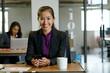 Portrait of businesswomen sitting at desk, holding smartphone, smiling