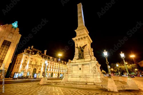 Plakat Popularny obelisk w Praca dos Restauradores lub Plac Restauracji na cześć Portugalskiej Niepodległości od Hiszpanii w centrum Lizbony, Portugalia. Spektakularny nocny krajobraz miejski.