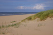 Sandstrand mit Meerblick aus der Düne mit Dünengras im Wind