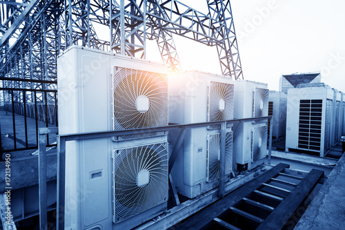 Valokuva  Air conditioner units (HVAC) on a roof of industrial building with blue sky and clouds in the background