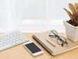 Minimal workspace,computer,smartphone,notebook,pencil and eyeglasses on wood table