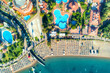 Aerial view of transparent turquoise sea, beautiful sandy beach with colorful chaise-lounges, boats, green trees, pool, hotels, buildings at sunrise in Icmeler, Turkey. Summer landscape. Top view.