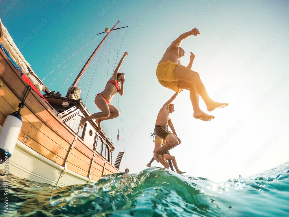 Fototapety, obrazy: Happy friends diving from sailing boat into the sea - Young people jumping inside ocean in summer excursion day - Vacation, youth and fun concept - Main focus on left man - Fisheye lens distortion