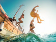 canvas print picture Happy friends diving from sailing boat into the sea - Young people jumping inside ocean in summer excursion day - Vacation, youth and fun concept - Main focus on left man - Fisheye lens distortion