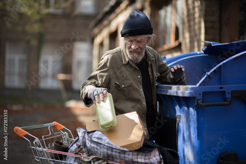 Homeless man searching for empty bottles and other stuff for recycle Fototapeta