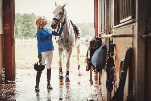 Photographie Middle-aged woman with her horse in a stall