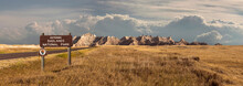Landscape Panorama Of Badlands Rocky Mountain Range, Clouds, And Grassland With Sign